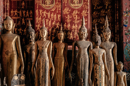 APR 5 Luang Prabang, Laos - Antique old wooden and gold Buddha statues at Wat  Xieng thong museum.  Most Famous tourist attraction in World heritage zone Editorial