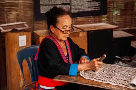 APR 4, 2018 Luang Prabang, Laos - Hilltribe Laotian woman working on Batik fabric painting. Culture tourism at Ock Pop Tok handicraft center Sajtókép