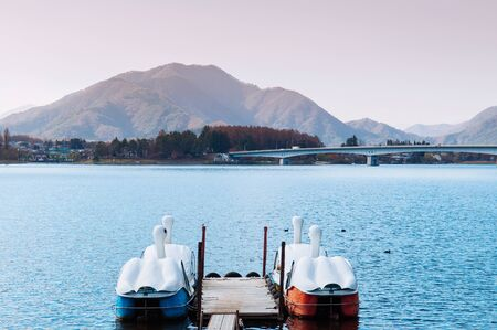 Beautiful Lake Kawaguchiko in winter with swan water bike boats at wooden pier and Ohashi bridge. Yamanashi - Japan