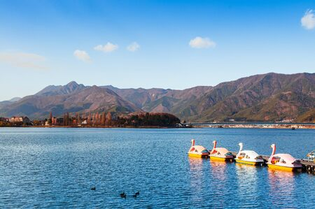 Beautiful Lake Kawaguchiko in winter with swan water bike boats and mountains view. Yamanashi - Japan