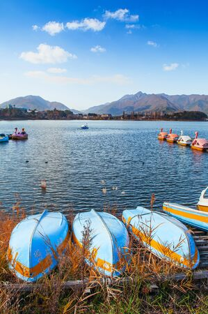 Beautiful Lake Kawaguchiko in winter with row boat stranded on shore and water bike boats at wooden pier in background. Yamanashi - Japan Stock Photo
