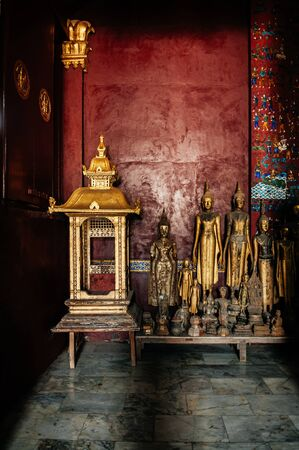 Luang Prabang, Laos - Antique old wooden and gold Buddha statues at Wat  Xieng thong museum.  Most Famous tourist attraction Editorial