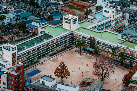 Tokyo, Japan - Aerial view of high school buildings in residential area of Ishikawa district with football field. Outer area of Tokyo Editorial