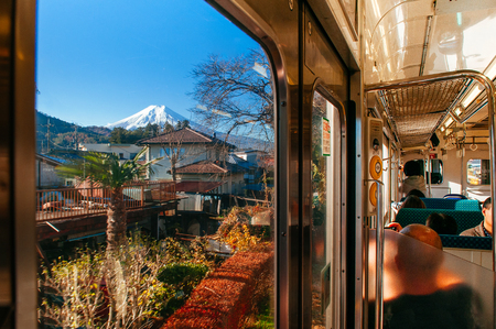 Fujiyoshida, Japan - NOV 30, 2018 : Snow covered Mount Fuji behind local town along train route from Tokyo to Kawaguchiko seen through train window with tourist sit at seat. Editorial