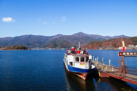Yamanashi, Japan - NOV 30, 2018 : Lake Kawaguchiko vintage scenic tourist boat at pier with mountain range and Kawaguchiko Ohashi bridge in background. Editorial