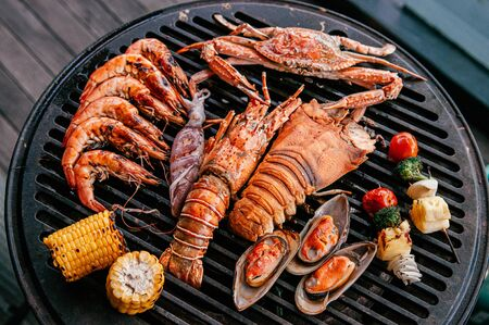 Lobster, rock lobster and mix seafood barbecue cooking on grill, seafood dinner party concept