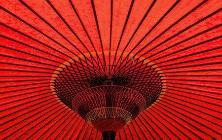 Vibrant red colour vintage retro traditional Japanese or asian paper cotton parasol umbrella background Stockfoto