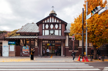 Tokyo, Japan - DECEMBER 5, 2018 : Harajuku station vintage building with people on sidewalk, pedestrain crosswalk and yellow Gingko tree in front of station in autumn.