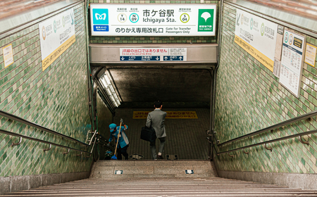 Tokyo, Japan - DECEMBER 5, 2018 : Tokyo subway entrance to underground passage retro interior tiles wall with business man walking down and worker cleaning stairs