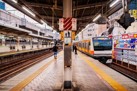 Tokyo, Japan - DECEMBER 5, 2018 : JR Chuo line train approaching Kanda station platform with few passengers waiting behind yellow line. Редакционное