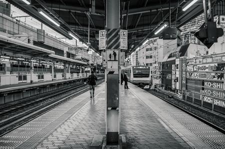 Tokyo, Japan - DECEMBER 5, 2018 : JR Chuo line train approaching Kanda station platform with few local Japanese passengers waiting.