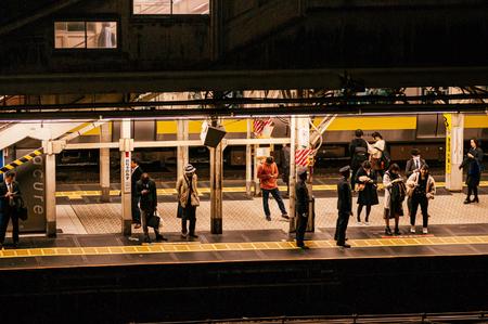 Tokyo, Japan - December 4, 2018 : Tokyo JR Chuo line train Ochanomizu station and people waiting on platform at night, image taken from high angle. Редакционное
