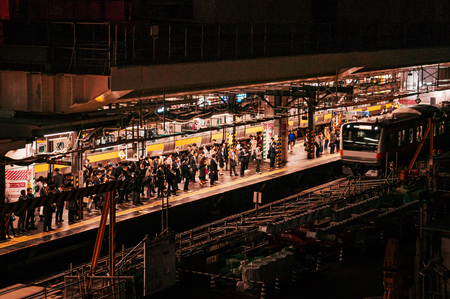 Tokyo, Japan - December 4, 2018 : Tokyo JR Chuo line train approching Ochanomizu station and many people waiting on platform at night, image taken from high angle.