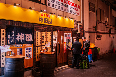 Tokyo, Japan - DECEMBER 4, 2018 : Izakaya bar and night street restaurant with neon signs and local people in front of Kanda JR station