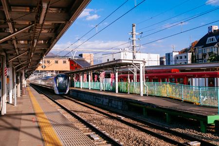 Oysuki, Japan - NOV 30, 2018 : Japan Azusa or Kaji Express train at Otsuki station platform under warm sunlight in winter. Interchange station between JR and Fujikyu - Fuji Tozan Densha line.