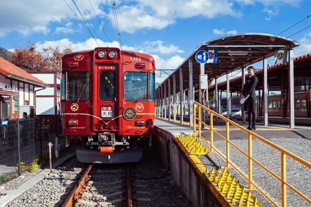 Otsuki, Japan - NOV 30, 2018 : Red Tourist train Fuji Tozandensha with female conductor at Kawaguchiko station platform. Most famous tourist train on Mount Fuji view route.