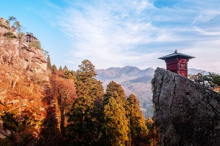 Nokyodo red sutra repository building on rock cliff in evening at Yamadera Risshaku ji temple. Yamagata - Japan