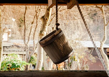 Old antique Water well wooden bucket with rope hanging above the hole
