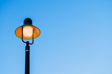 Vintage retro electric light pole with blue evening sky background with copy space on one side for design work