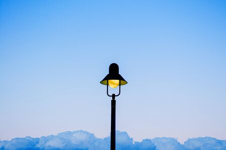 Vintage retro electric light pole with blue evening sky background with copy space on both side for design work 写真素材