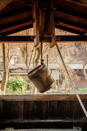 Old antique Water well wooden bucket with rope hanging above the hole Stok Fotoğraf