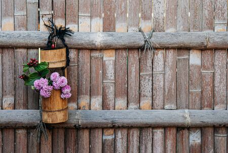 Flower in bamboo vase hanging on bamboo fence background - Japanese Ikebana with chrysanthemum flower and leaves