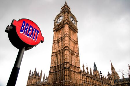 Brexit concept - Red Brexit sign post with Big Ben British Parliament building and white foggy background. UK Political and economic crisis