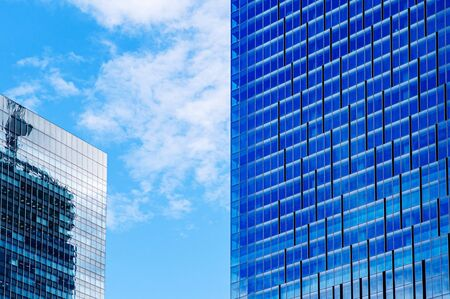 Modern glass wall skyscrapers in business district against bright blue sky with clouds, Tokyo - Japan. Financial and business background concept