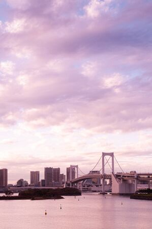 Odaiba Rainbow bridge and Tokyo bay view at evening sunset with cityscape in background under pinkish sky