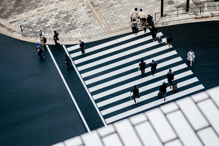 DEC 6, 2019 Tokyo, Japan - Modern city pedestrain crosswalk from aerial view. Street photo of Tokyo downtown business district with people.