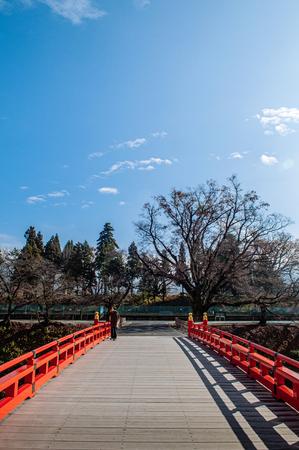 DEC 4, 2018 Aizu Wakamatsu, JAPAN - Aizu Wakamatsu Tsuruga Castle Rokabashi red bridge under winter blue sky. Fukushima Samurai lord fortess in Edo period