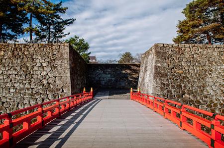 DEC 4, 2018 Aizu Wakamatsu, JAPAN - Aizu Wakamatsu Tsuruga Castle Rokabashi red bridge and high stone wall. Fukushima Samurai lord fortess in Edo period