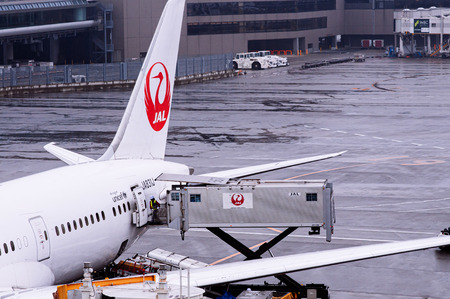 DEC 6, 2018 Narita, Japan -  Airplane of JAL Airline during  meal loading under raining bad weather at Tokyo Narita International airport with ground crew working at apron area Editöryel