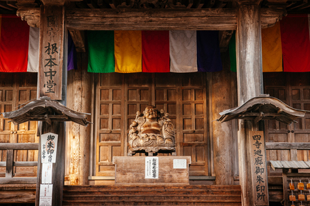 DEC 3, 2018 - Yamagata, Japan - Japanese carved wood smiling Buddha statue with old wood wall and colourful flag of Konpon Chudo main hall in Yamadera Risshakuji temple 報道画像