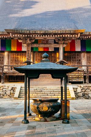 DEC 3, 2018 - Yamagata, Japan - Konpon Chudo main hall incense pot in Yamadera Risshakuji temple with old wood wall and colourful Buddhism flags