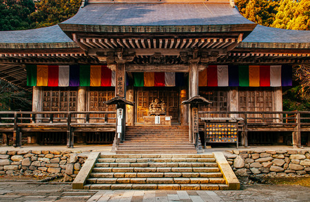 DEC 3, 2018 - Yamagata, Japan - Konpon Chudo main hall in Yamadera Risshakuji temple and Japanese carved wood smiling Buddha statue with old wood wall and colourful Buddhism flags 報道画像