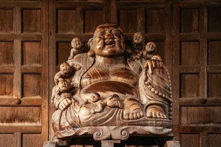 DEC 3, 2018 - Yamagata, Japan - Japanese carved wood smiling Buddha statue with old wood wall in Yamadera Risshakuji temple