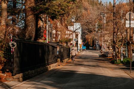 DEC 3, 2018 - Kakunodate, Japan - Kakunodate old Samurai town famous vintage Edo village with big tree along peaceful street and people riding bicycle. Akita, Tohoku region