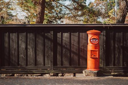 DEC 3, 2018 - Kakunodate, Japan - Red vintage Japanese mail letter postbox and black wooden wall in Kakunodate old Samurai town of  Akita, Tohoku region