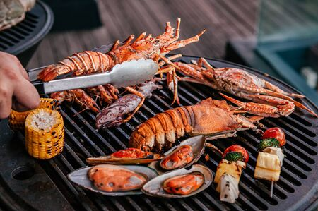 Lobster, rock lobster and mix seafood barbecue cokking on grill - seafood dinner party concept Фото со стока