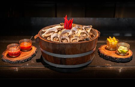 Fresh whole marine Fine de claire oysters in oak wood bucket with lime, lemon and vinegar sauce - dark tone food image