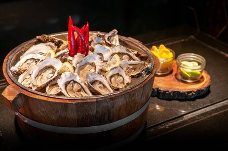 Fresh whole marine Fine de claire oysters in oak wood bucket with lime and lemon - dark tone food image Banque d'images