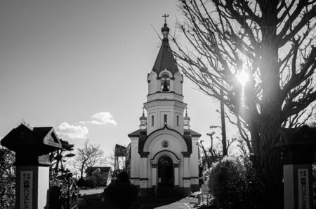 DEC 2, 2018 Hokkaido, Japan - Hakodate Orthodox Church - Russian Orthodox church bell tower in winter under clear sky silhouette against sun with ray of light. Motomachi district.