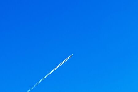 Airplane white smoke contrail tail at high speed cuising at high speed in blue winter sky