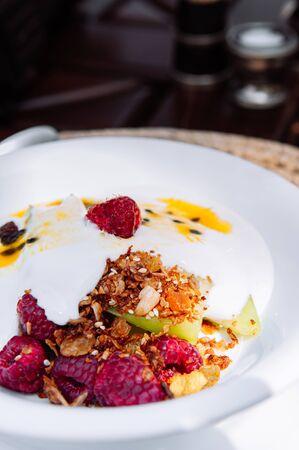 Breakfast berry yogurt mousli with raspberry apple almond and fresh sour sweet passion fruit sauce, light healthy breakfast