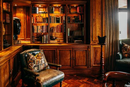 JUN 19, 2011 Serengeti, Tanzania - Luxury African Safari lodge reading room  interior with old vintage leather armchairs under warm light and antique books decoration