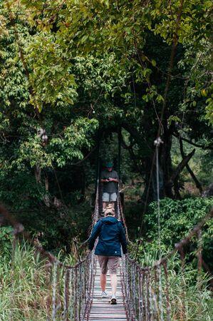 JUN 22, 2011 Serengeti, Tanzania - Tourists enjoy wildlife walk on suspension bridge in Serengeti savanna forest - African wild travel in green forest Reklamní fotografie