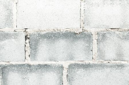 Grey coloured light tone rough grungy textured old concrete block brick wall background wallpaper