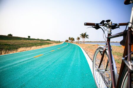 Vintage road bicycle on street with nature field view. Riding sport and heathy outdoor activity