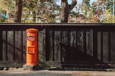 Red vintage Japanese mail letter postbox and black wooden wall